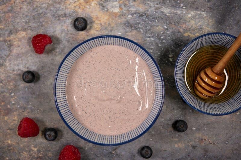 简单的acai碗围拢用莓、蓝莓和蜂蜜 免版税图库摄影