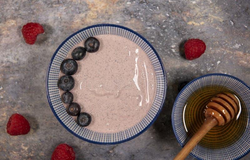 简单的acai碗围拢用莓、蓝莓和蜂蜜 库存照片