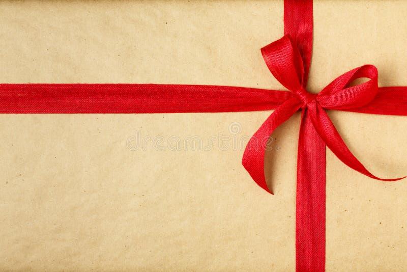 简单,欢乐与能承受的被回收的卡拉服特包装纸的圣诞礼物当前背景和明亮的红色丝带弓 库存图片