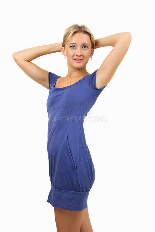 简而言之妇女,紧身,蓝色礼服,握在她的头后的手。 库存图片