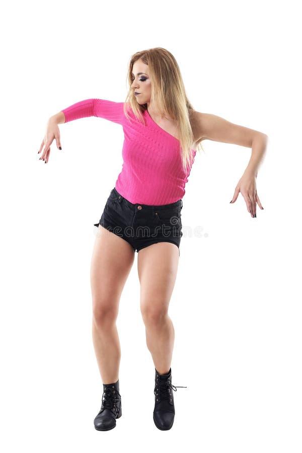 简而言之有吸引力的白肤金发的妇女跳舞爵士乐舞蹈,靴子和桃红色衬衣 免版税库存照片