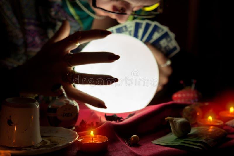 算命者妇女和水晶球的手与占卜用的纸牌 免版税图库摄影