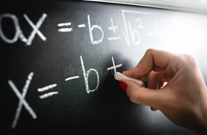 算术等式、作用或者演算对黑板 在黑板的老师文字在教训和演讲期间在学校 免版税库存照片