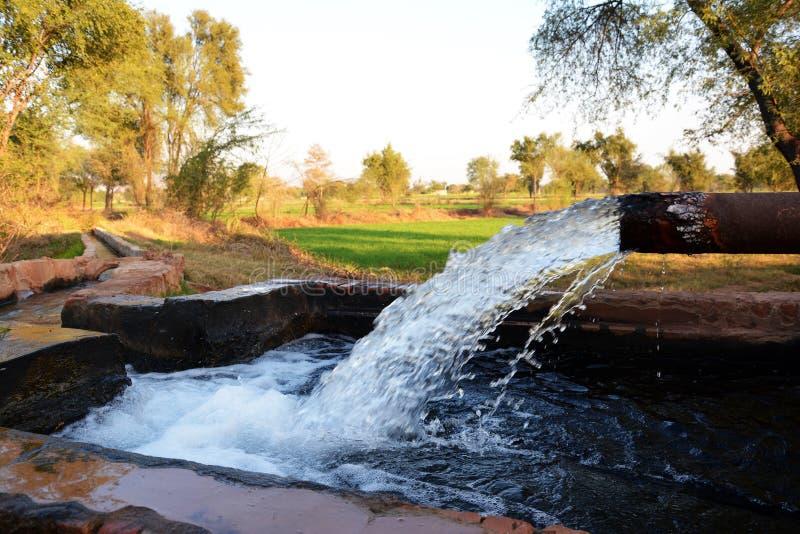 管井的出口对一个临时水库在巴基斯坦的一个小村庄 免版税库存照片