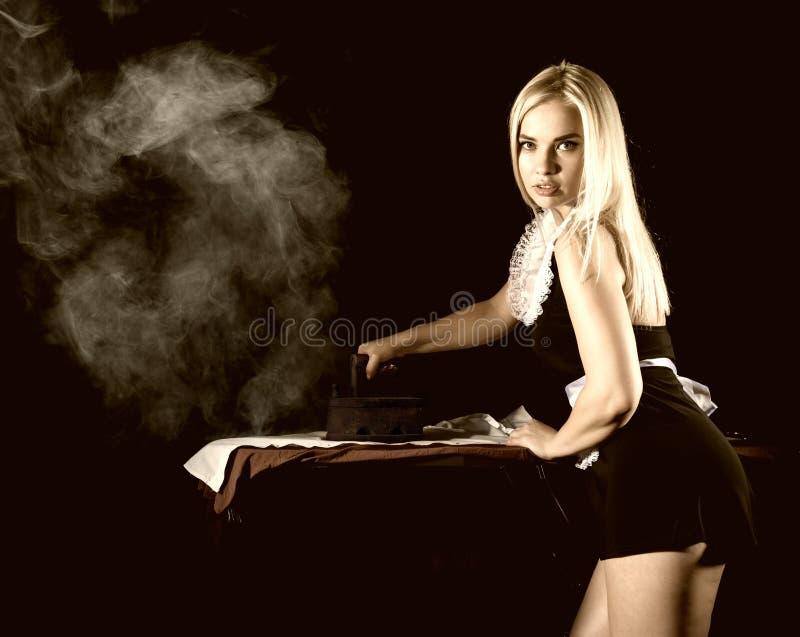 管家衣服的,有老铁的电烙的白色衬衣性感的白肤金发的妇女 在黑暗的背景的减速火箭的样式 免版税库存照片