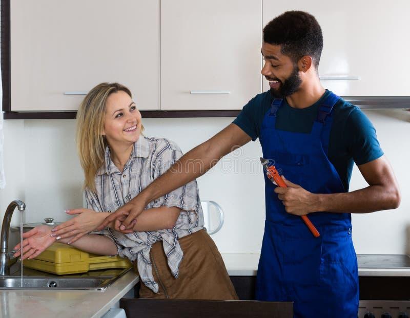 水管工和主妇在厨房里 免版税库存图片