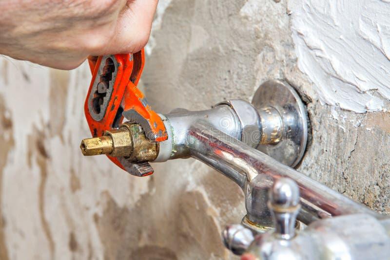 水管工定象水龙头阀门在厨房,用户钳子板钳里 免版税库存照片