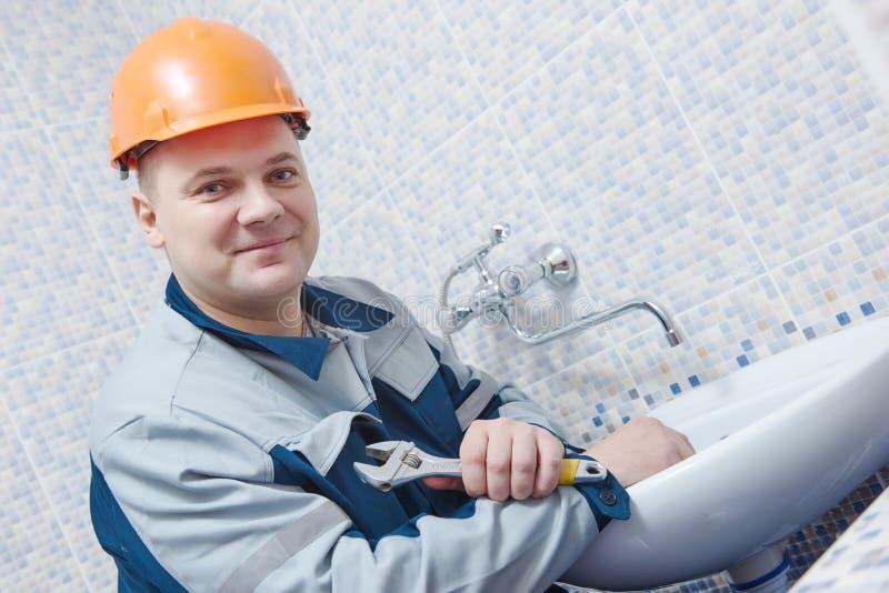 水管工服务 安装明三联式浴缸水嘴的工作者在卫生间 库存图片