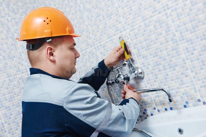 水管工服务 安装明三联式浴缸水嘴的工作者 库存照片