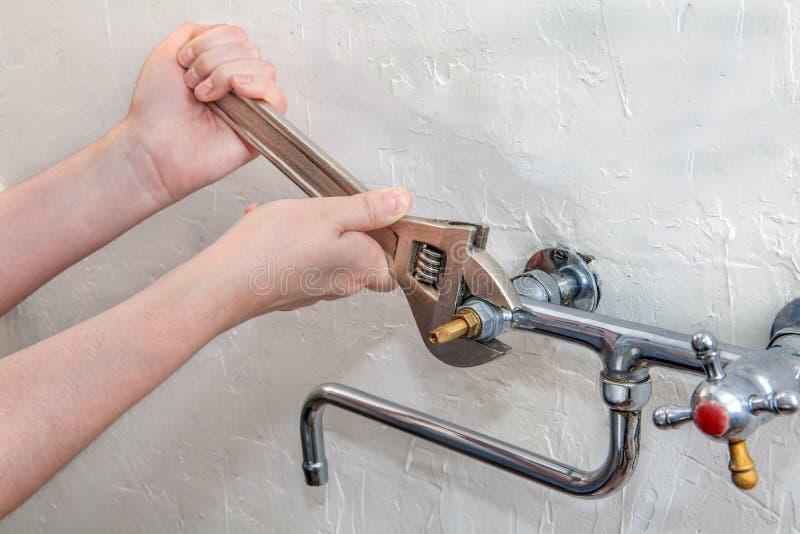 水管工递定象与扳手,关闭的水龙头 免版税库存照片