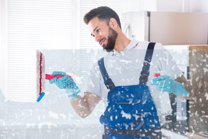 管理员与橡皮刮板的清洁窗口 免版税库存图片