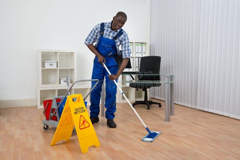 管理员与湿地板标志的清洁地板 免版税库存照片