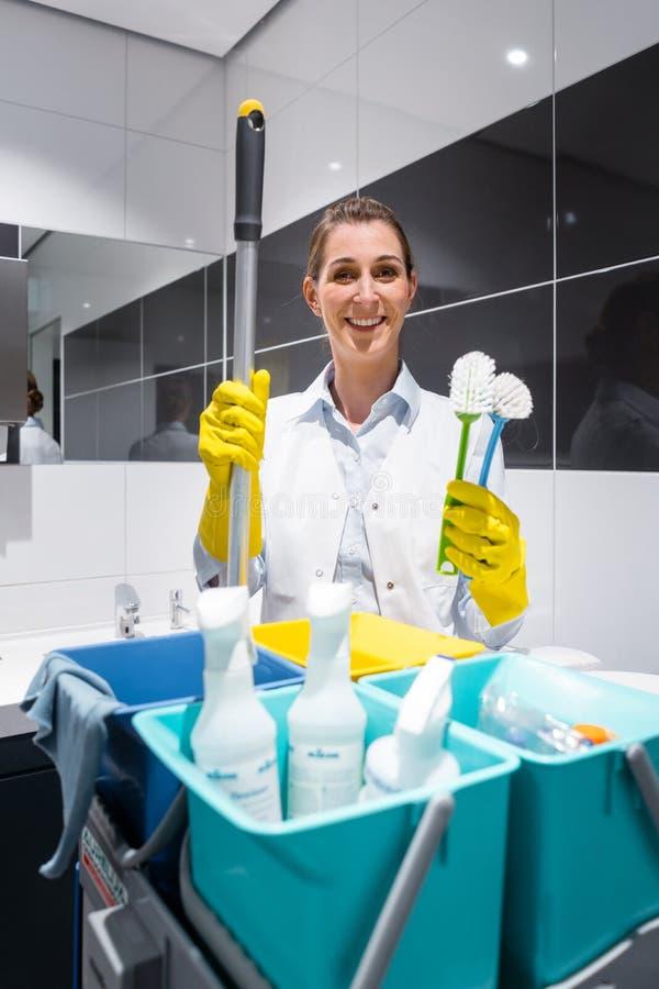 管理员或打杂的女佣人有她的工作的用工具加工看照相机在洗手间 免版税库存照片