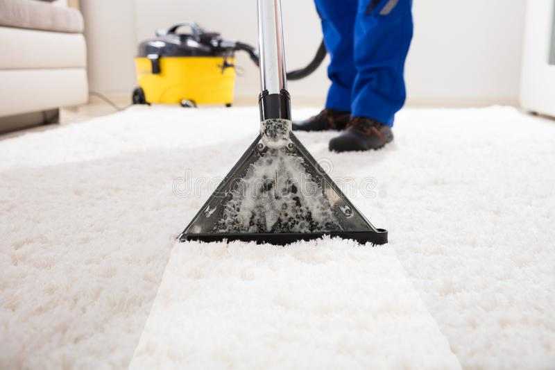 管理员有吸尘器的清洁地毯 免版税图库摄影