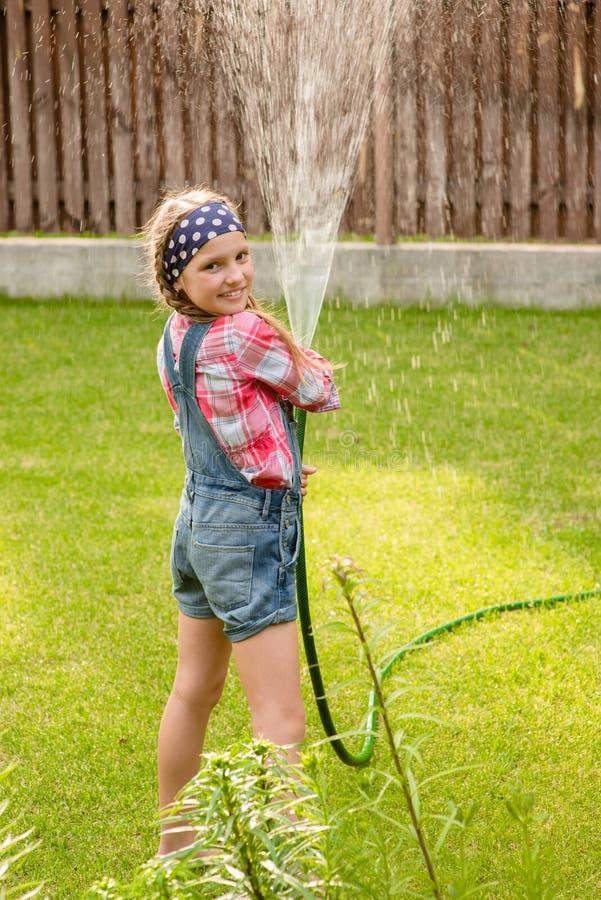 从水管的愉快的逗人喜爱的小女孩倾吐的水 免版税库存照片