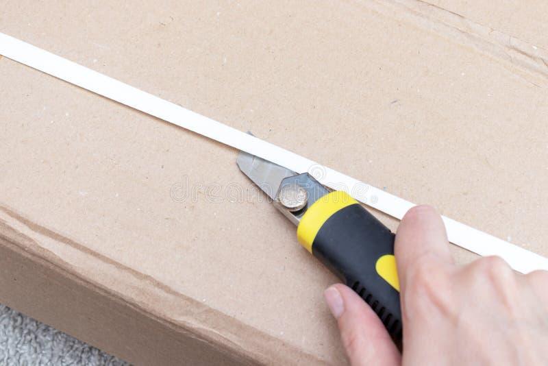 箱中取出有新的家具的一个纸板箱有建筑或办公室刀子的-移动向新房和购买新的家具 免版税库存图片