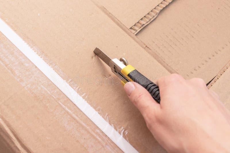 箱中取出有新的家具的一个纸板箱有建筑或办公室刀子的-移动向新房和购买新的家具 库存图片