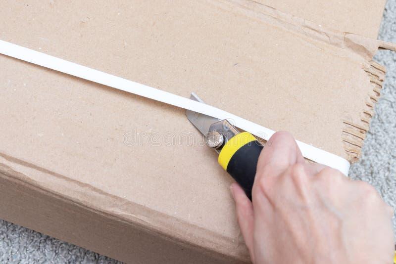 箱中取出有新的家具的一个纸板箱有建筑或办公室刀子的-移动向新房和购买新的家具 库存照片
