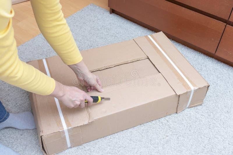 箱中取出有新的家具的妇女一个纸板箱有建筑刀子的-搬到新房和购买新的家具 免版税库存照片
