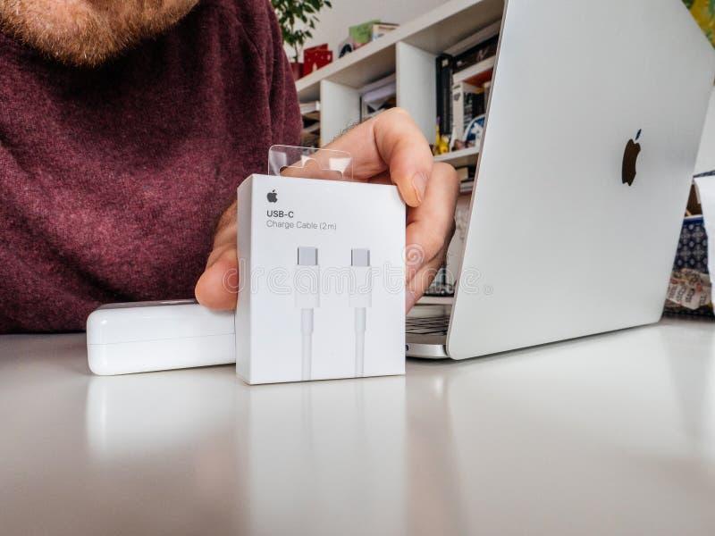 箱中取出苹果电脑缆绳力量膝上型计算机的人 免版税图库摄影