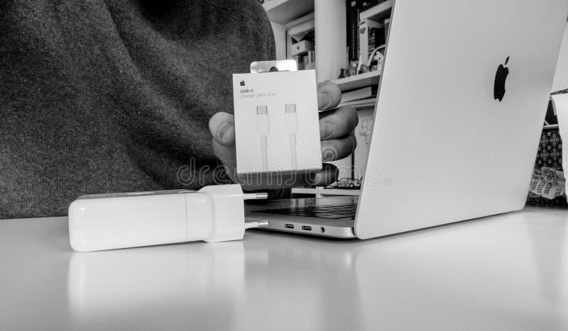 箱中取出苹果电脑USB-C缆绳的人 免版税图库摄影