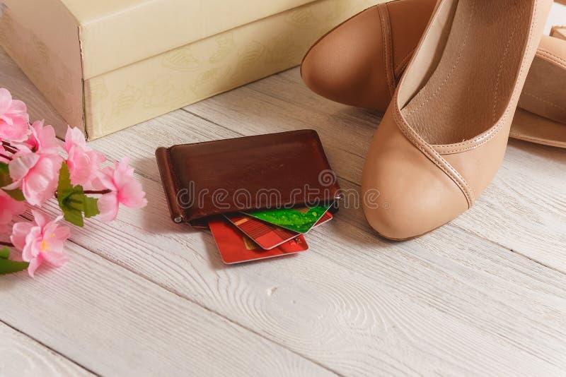 箱子、钱包、说谎在白色木背景的信用卡和妇女鞋子 免版税库存照片