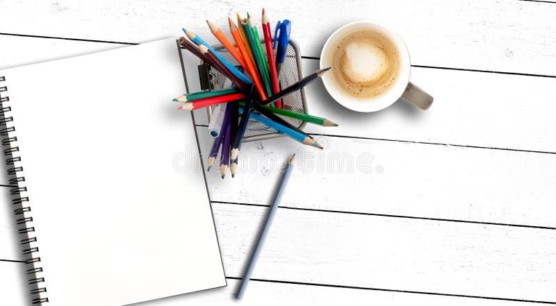 箱子充满色的铅笔和写生簿或者在土气白色木桌上的螺旋笔记薄 免版税库存图片