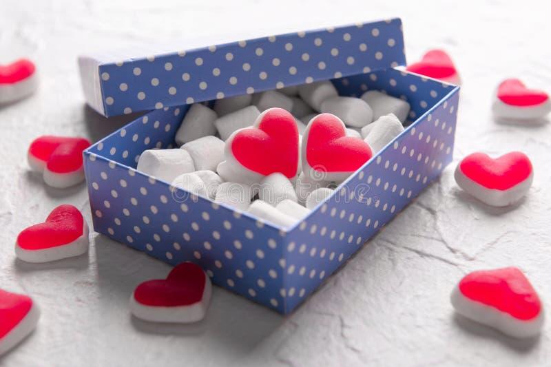 箱子用蛋白软糖和心形的果冻糖果在轻的织地不很细背景 免版税库存图片