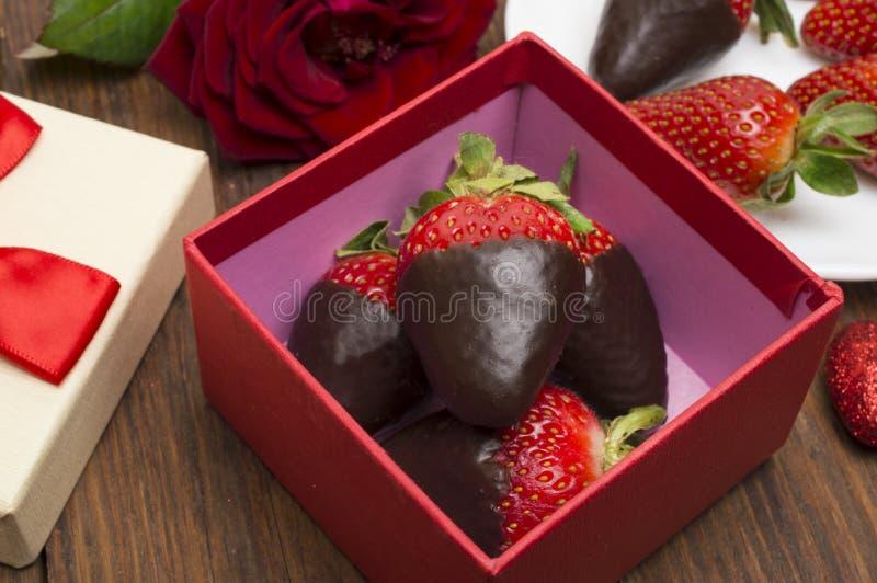 箱子用鲜美巧克力浸洗了花草莓和花束在桌上的 免版税库存照片