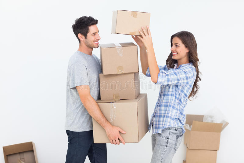 给箱子的妇女她的丈夫,当他们移动时 免版税库存照片