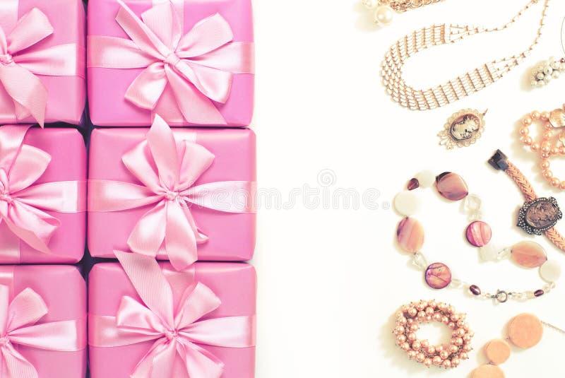 箱子行有礼物装饰丝带缎的鞠躬妇女首饰珍珠项链镯子A顶视图的桃红色时装配件 库存照片