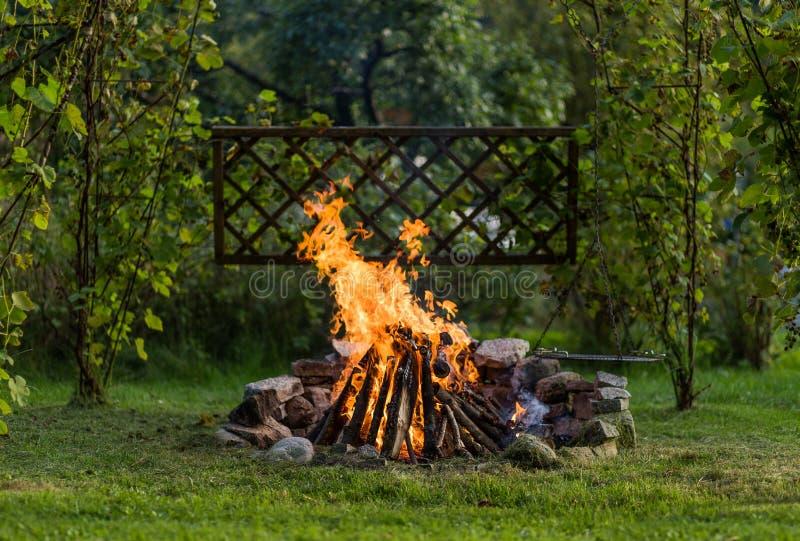 篝火在有格床的庭院里准备好BBQ 库存照片