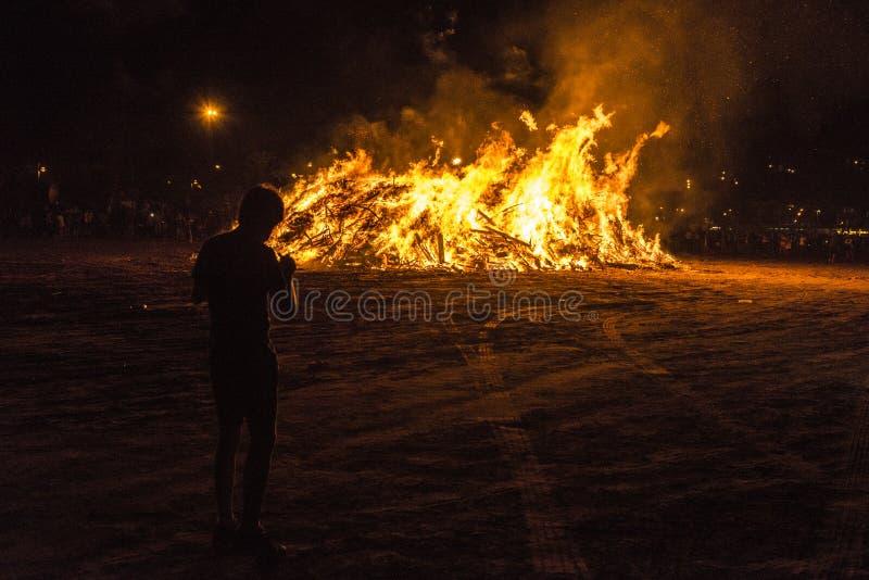 篝火的男孩在一个海滩在晚上,肋前缘Brava,西班牙 免版税图库摄影