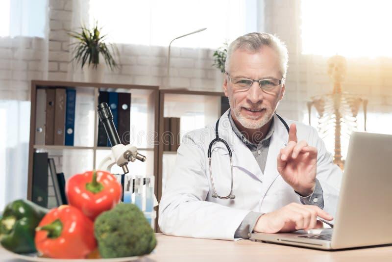 篡改坐在书桌在有显微镜和听诊器的办公室 人研究膝上型计算机 免版税库存照片
