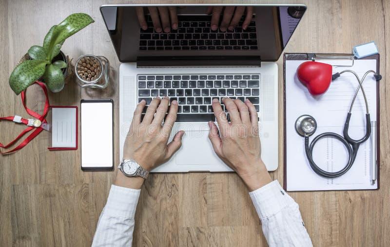 篡改工作在办公桌和使用便携式计算机 免版税库存照片