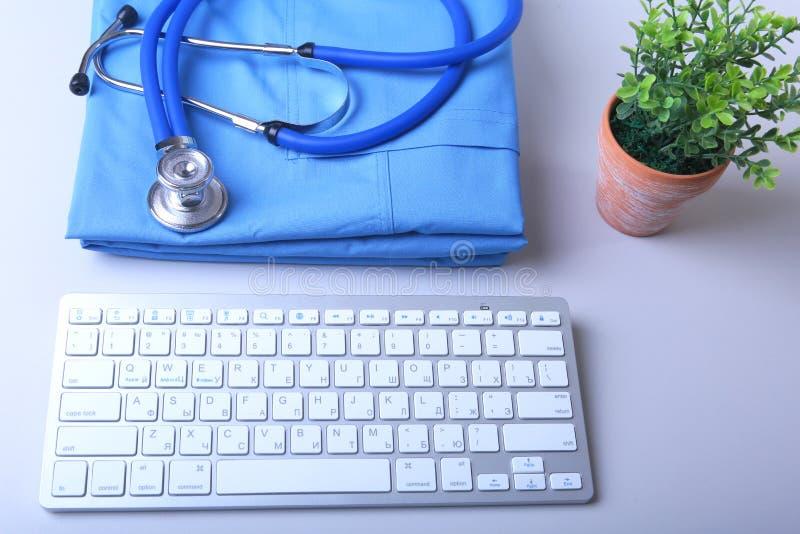 篡改有医疗听诊器和键盘的外套在书桌上 库存照片