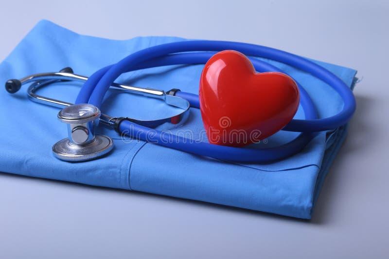 篡改有医疗听诊器的外套和在书桌上的红色心脏 库存照片