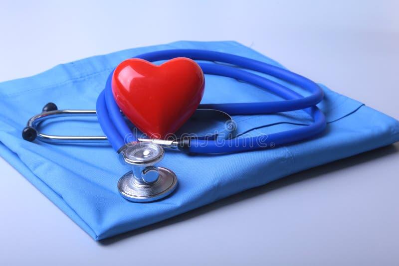 篡改有医疗听诊器的外套和在书桌上的红色心脏 免版税库存图片