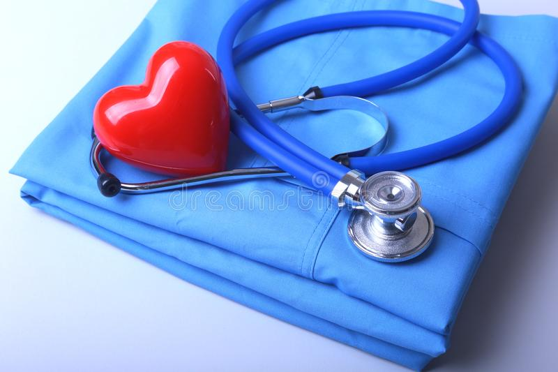 篡改有医疗听诊器的外套和在书桌上的红色心脏 免版税库存照片