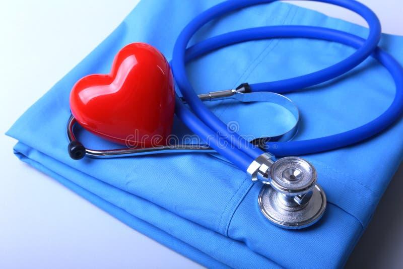 篡改有医疗听诊器的外套和在书桌上的红色心脏 免版税图库摄影