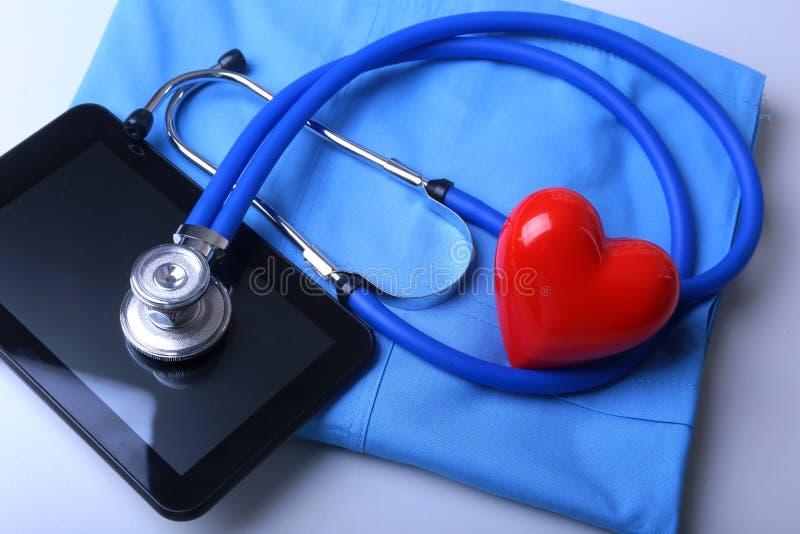 篡改有医疗听诊器的外套和在书桌上的红色心脏 库存图片
