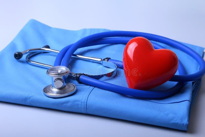 篡改有医疗听诊器的外套和在书桌上的红色心脏 图库摄影