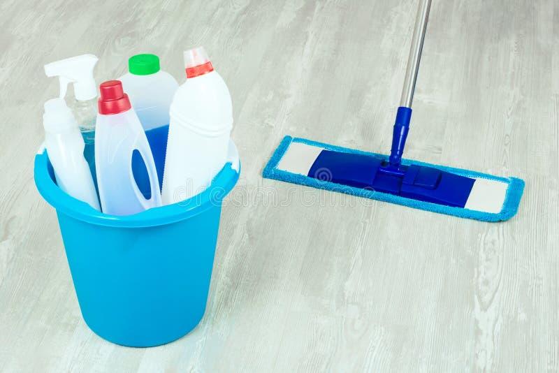 篮子和拖把有品种清洁产品的在木地板上 清洁概念洗碗盘行为液体海绵 免版税库存图片