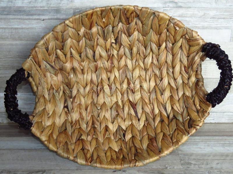 篮子生长在水中的由羽根制成 在被漂白的橡木背景的美丽的手工制造被编织的竹子/藤茎篮子 顶视图 免版税库存照片
