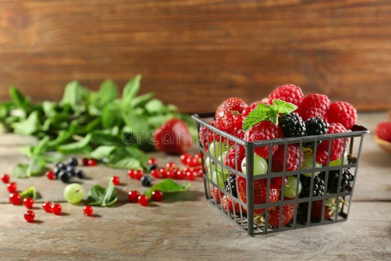 篮子用在木桌上的可口莓果 库存照片