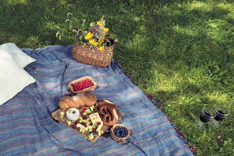 篮子用酒和花面包和乳酪在一条野餐毯子在绿草在地面上 免版税库存图片