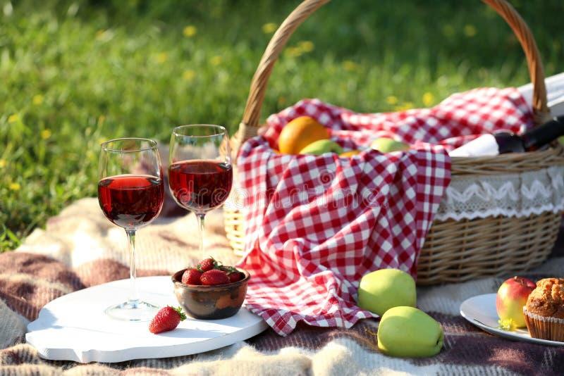 篮子用食物和杯在为浪漫野餐准备的格子花呢披肩的酒在公园 免版税库存照片