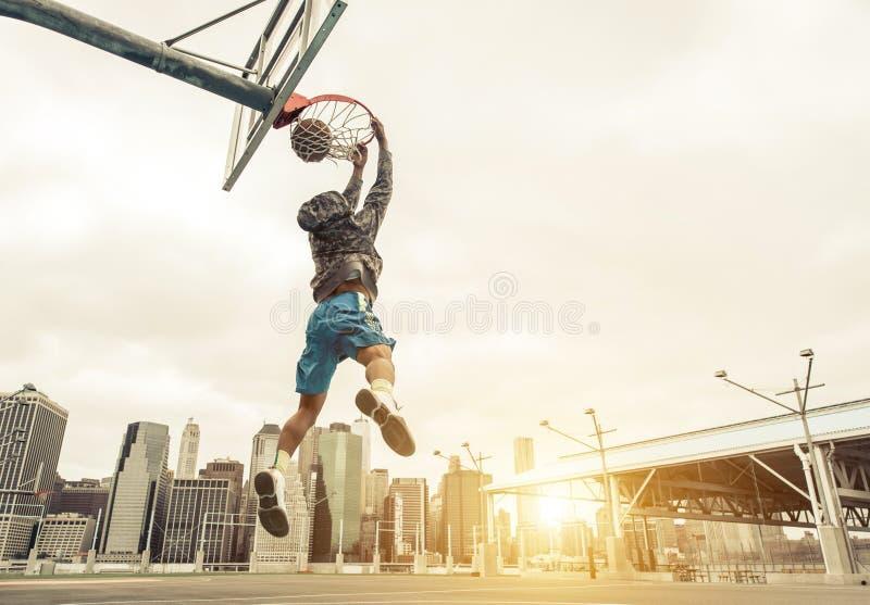篮球做后方灌篮的街道球员 免版税库存照片