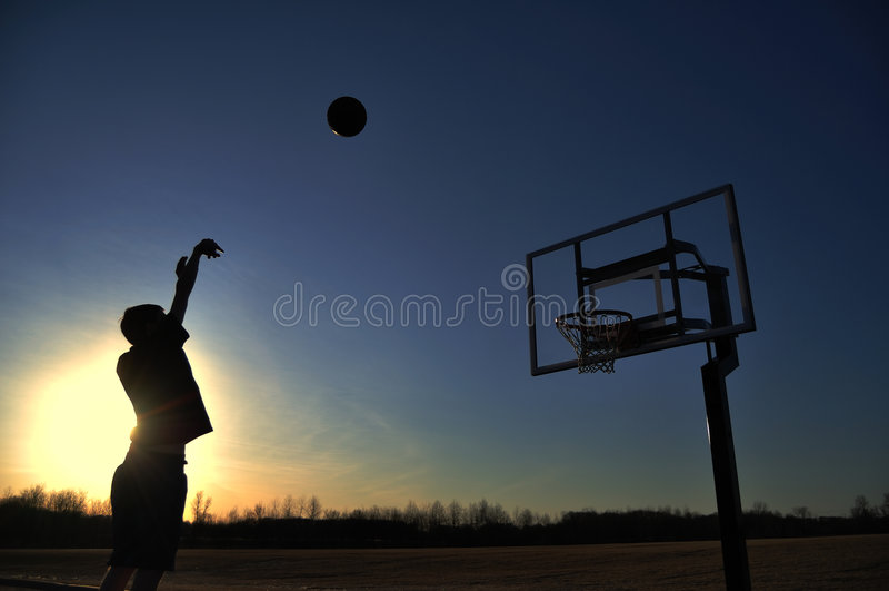 篮球男孩青少年射击的剪影 库存照片