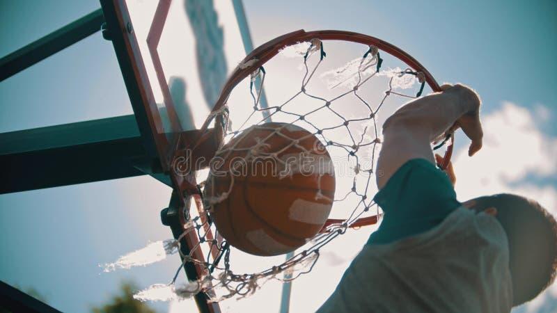 篮球篮-一个人投掷球和它在目标得到-灌篮 库存照片